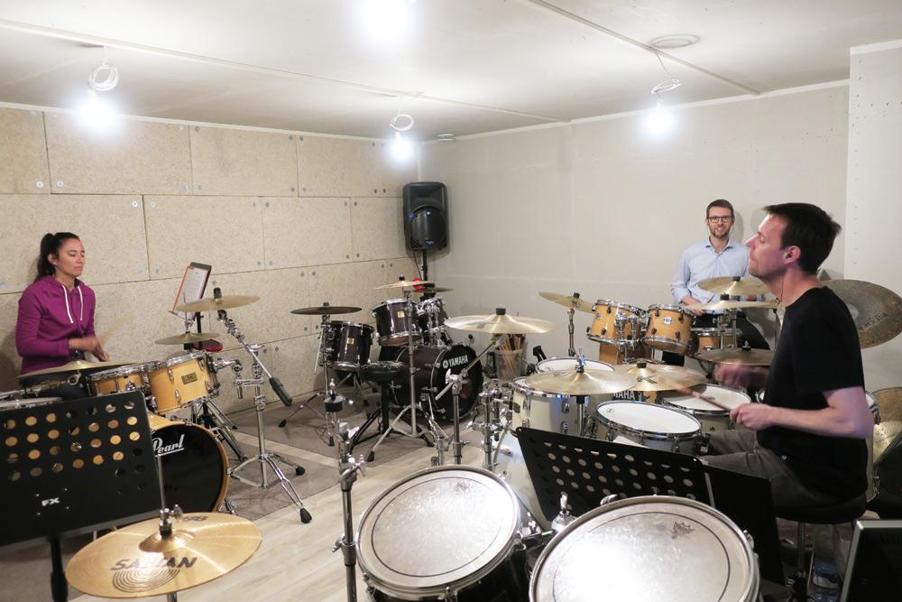un professeur de batterie et ses élèves dans l'école de musique Drums & Co Genève