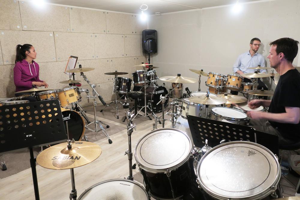 un professeur de batterie et ses élèves dans l'école de musique Drums & Co à Genève