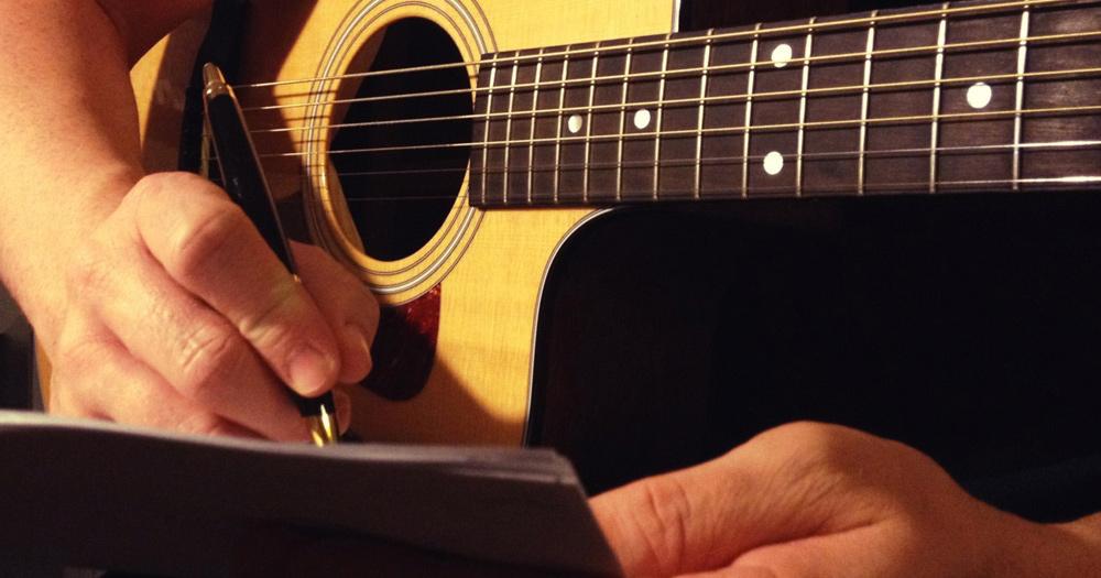 un homme qui écrit en tenant sa guitare