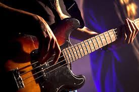 une personne qui joue de la basse dans l'école de musique Drums&Co