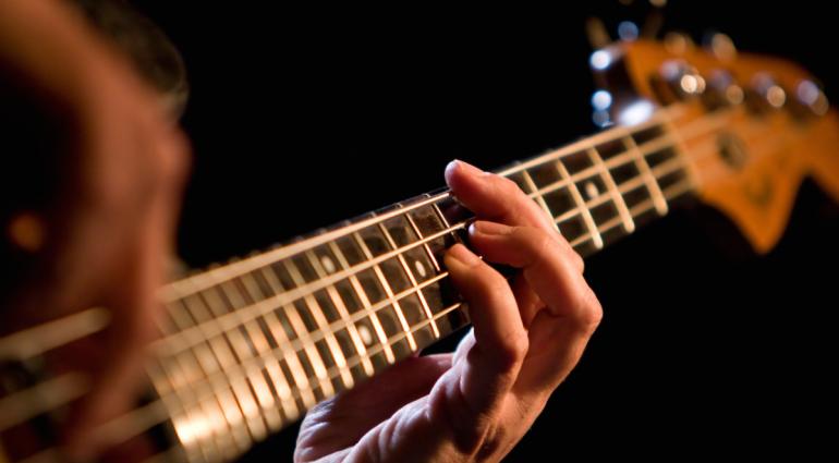 une personne qui joue de la basse à Genève