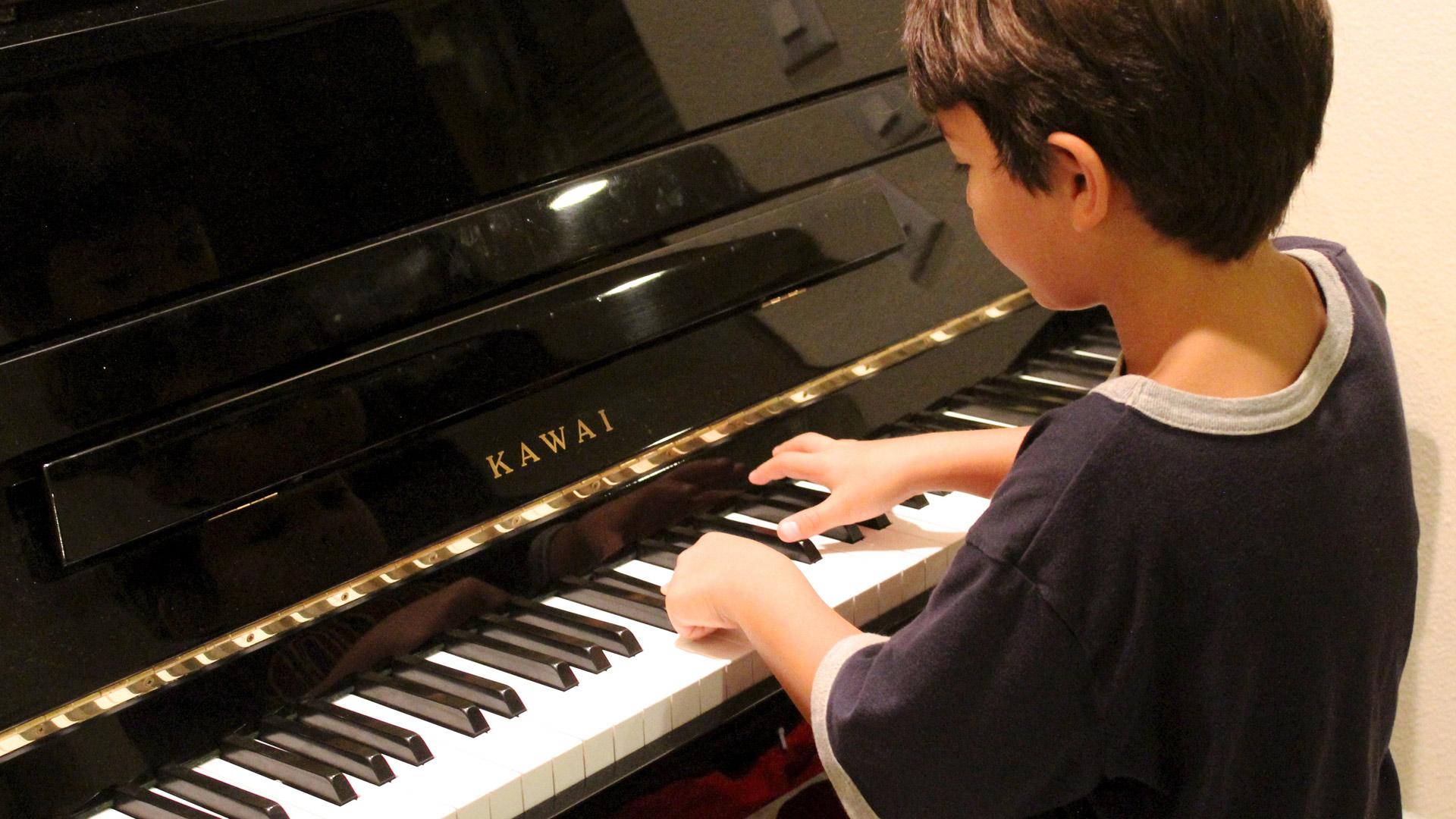 un garçon qui joue du piano
