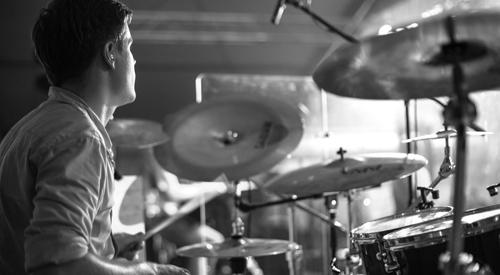 un jeune homme qui joue de la batterie durant un cours